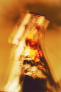 Galerie Ahlemann zeigt ein abstraktes Foto von Claudia Maria Weiser in überwiegend gelb- und braunfarbenen Tönen, auf dem schemenhaft der Förderturm von Schacht 12 des UNESCO Welterbes Zeche Zollverein in Essen zu erkennen ist.
