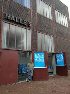 Ein Foto von Ralf Lindenau in der Tür zur Halle 5, Zeche Zollverein stehend bei der ersten Pause zum Aufbau des Standes der Galerie Ahlemann (Galerie für abstrakte Fotokunst) bei der Contemporary Art Ruhr.