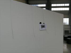Anfänge des Messeaufbaus: Fünf Stahlseile für das Aufhängen der Bilder sowie der Messeplan sind auf einer der vier Messewände des Standes der Galerie Ahlemann zu sehen.