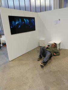 Ein Foto von Ralf Lindenau auf dem Boden mit einem Akkuschrauber liegend, um das Untergestell für den Präsentationsbildschirm aufzubauen und an der Standwand zu befestigen.