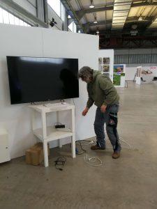 Ein Foto von Ralf Lindenau nach dem Aufbau und der Befestigung des Gestells und des Präsentationsbildschirms, gerade dabei, die Stromanschlüsse zu verlegen und anzuschließen.