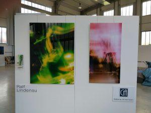 Das Foto zeigt eine der vier Wände des Messestandes der Galerie Ahlemann, an denen zwei abstrakte Fotokunstwerke von Ralf Lindenau angebracht sind. wobei das linke in gelb-grünen und das rechte in überwiegend rosa und braunen Farbtönen gehalten ist.