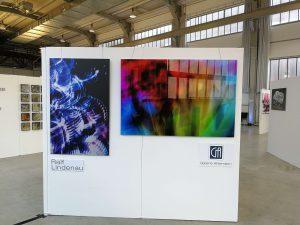 Das Foto zeigt eine weitere der vier Wände des Messestandes der Galerie Ahlemann, an denen zwei abstrakte Fotokunstwerke von Ralf Lindenau angebracht sind. wobei das linke in überwiegend blauen und schwarzen Farbtönen und das rechte in bunten Farben gehalten ist.