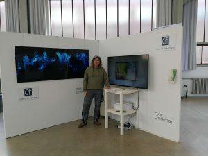 Das Foto zeigt Ralf Lindenau auf dem Messestand neben der erfolgreich laufenden Präsentationstechnik.
