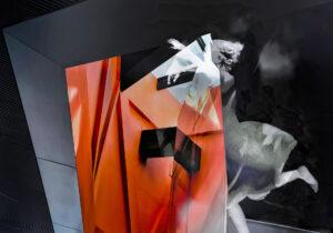 Galerie Ahlemann zeigt ein abstraktes Foto von Petra Jaenicke welchesvor einem überwiegend dunkelgrauen Hintergurnd die Silhouette einer dynamischen Frauenfigur in grauen Farbtönen zeigt sowie ein rotes architektonisch anmutendes Element.