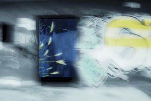 Galerie Ahlemann zeigt ein abstraktes Foto von Petra Jaenicke in überwiegend blauen und weißen Farbtönen, auf dem schemenhaft auf der rechten Seite ein Teil eines Graffitis zu sehen ist und auf der rechten Hälfte der linken Seite ein hochkant stehendes Bild auf dem die oberen Enden einiger Getreidehalme zu erkennen sind.