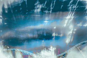 Galerie Ahlemann zeigt ein abstraktes Foto von Petra Jaenicke in blauen und weißen Farbtönen. Vor dem abstrakten blau-weißen HIntergrund sieht man im untersten Viertel des Bildes eine geschwungene, quer über das Bild laufende Schiene (wie etwa von einer Achterbahn).