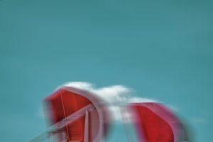 Galerie Ahlemann zeigt ein abstraktes Foto von Petra Jaenicke. Auf dem unteren Drittel des Bildes vor einem hellblauen Hintergrund ragen zwei rote halbkreis-ähnliche Gebilde in das Bild hinein. Hinter den roten Objekten zeichnet sich eine kleine weiße Wolke ab.