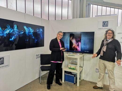 Das Foto zeigt die zwei Innenseiten des Messestandes der Galerie Ahlemann mit der Galeristin Andrea Ahlemann und dem ausstellenden Fotokünstler Ralf Lindenau.