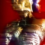 Galerie Ahlemann zeigt ein abstraktes Foto von Ralf Lindenau in der Kategorie Wahnbild, auf welchem man einen menschlich wirkenden Oberkörper in metallischen Farbtönen vor einem roten Hintergrund erkennen kann.