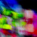 Galerie Ahlemann zeigt ein abstraktes Foto von Ralf Lindenau in der Kategorie Wahnfarben in überwiegend helleren bunten Farbtönen vor einem dunklem Hintergrund.