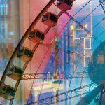Galerie Ahlemann zeigt ein abstraktes Foto der Fotokünstlerin Hasina Khan auf dem in verschiedenen Farben ein Ausschnitt des Hngkonger Riesenrades zu sein ist, kollagiert mit Hongkonger Häuserfassaden im Hintergrund.