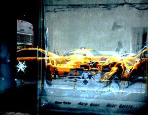 Galerie Ahlemann zeigt ein abstraktes Foto der Fotokünstlerin Hasina Khan, welches in einer verschwommen Refklektion mehrere gelbe New Yorker Taxis vor einem grauen Hintergrund zeigt.