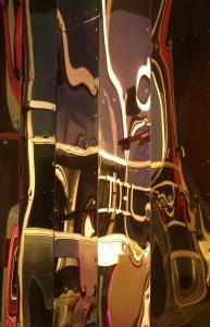 Galerie Ahlemann zeigt ein abstraktes Foto der Fotokünstlerin Hasina Khan, welches eine surreal-anmutende Spiegelung auf mehreren parellelverlaufenden, länglichen Metallplatten zeigt. Bei diesem Foto ist die Farbe Braun vorherrschend.