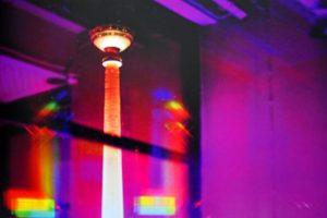 Galerie Ahlemann zeigt ein abstraktes Foto des Fotokünstlers Jochen Cerny in überwiegend violetten Farbtönen. Im Hintergrund ist bei dem Blick durch das Fenster in nächtlich surrealem Licht ein hoher, schmaler, angeleuchteter Turm zu erkennen.