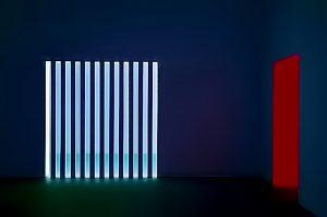 Galerie Ahlemann zeigt ein abstraktes Foto des Fotokünstlers Jochen Cerny in überwiegend blauen Farbtönen. Das Bild zeigt einen dunkelblauen Raum, dessen Rückwand durch eine türartige Öffnung mit elf Streben durchbrochen ist. Dies lässt in einen hellen, bläulichen Raum blicken. Die rechte Wand ist durch eine Türöffnung unterbrochen, deren hintere, sichtbare Innenwand dunkelrot erscheint.