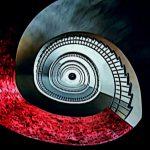 Galerie Ahlemann zeigt ein abstraktes Foto des Fotokünstlers Jochen Cerny in weißen, roten, grauen und schwarzen Farben. Das Foto zeigt ein spiralförmig, in das Zentrum des Bildes abwärts verlaufendes Treppenhaus.