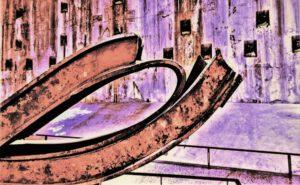 """Galerie Ahlemann zeigt ein abstraktes Foto von Nicki Garz aus der Konzeptreihe """"9 /11"""", auf dem in bräunlichen und violetten Farbtönen im Vordergrund ein verbogener Stahlträger und im Hintergrund eine Kontermauer, die der Explosion standgehalten hat, zu sehen sind."""