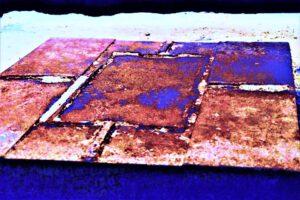 """Galerie Ahlemann zeigt ein abstraktes Foto von Nicki Garz aus der Konzeptreihe """"9 /11"""", auf dem im Boden die Umrisse eines Stützpfeilers zu sehen sind, in überwiegend bräunlichen und blauen Farbtönen."""