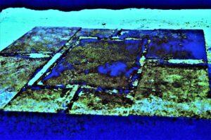 """Galerie Ahlemann zeigt ein abstraktes Foto von Nicki Garz aus der Konzeptreihe """"9 /11"""", auf dem im Boden die Umrisse eines Stützpfeilers zu sehen sind, in überwiegend blauen und türkisen Farbtönen."""
