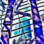 """Galerie Ahlemann zeigt ein abstraktes Foto von Nicki Garz aus der Konzeptreihe """"9 /11"""", auf dem in überwiegend blauen Farbtönen im Vordergrund zwei Stützpfeiler des alten World Trade Center zu sehen sind und im Hintergrund, durch das Fenster, der Neubau auf dem Ground Zero."""