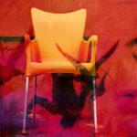 Galerie Ahlemann zeigt ein abstraktes Foto von Petra Jaenicke auf dem ein orangener Stuhl vor rotem Hintergrund, die von schattenhaften Vogelsilhouetten und einem menschlichen, auf dem Kopf stehenden Umriss durchzogen sind.