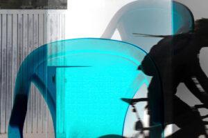 """Galerie Ahlemann zeigt ein abstraktes Foto von Petra Jaenicke aus der Konzeptreihe """"Ein Stuhl ist ein Stuhl"""" in grauen und türkisen Farbtönen, auf dem auch die Silhouette eines Fahrradfahrers zu erkennen ist."""