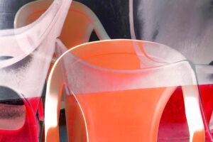 """Galerie Ahlemann zeigt ein abstraktes Foto von Petra Jaenicke aus der Konzeptreihe """"Ein Stuhl ist ein Stuhl"""" in hellrosa, orangen und roten Farbtönen vor einem dunklen Hintergrund."""
