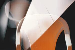 """Galerie Ahlemann zeigt ein abstraktes Foto von Petra Jaenicke aus der Konzeptreihe """"Ein Stuhl ist ein Stuhl"""" in weißen und orangefarbenen Tönen vor einem dunklen Hintergrund."""