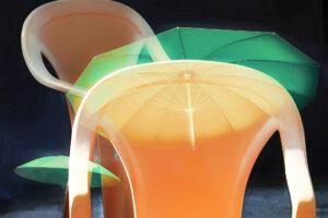 """Galerie Ahlemann zeigt ein abstraktes Foto von Petra Jaenicke aus der Konzeptreihe """"Ein Stuhl ist ein Stuhl"""" in orangen und grünen Farben vor einem dunklen Hintergrund."""