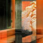 Galerie Ahlemann zeigt ein abstraktes Foto von Petra Jaenicke in organgen, schwarzen und weißen Farbtönen auf dem eine Zimmerecke mit einem Fenster und einer Sitzgelegenheit zu sehen ist. Das Bild wird mittige durch einen halben Frauenkopf durchbrochen.