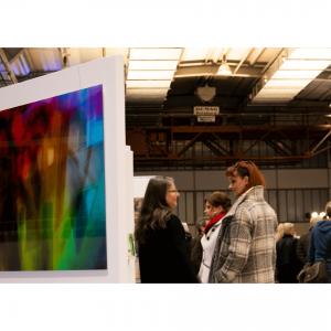 Das Foto zeigt einen Teil des Messestandes der Galerie Ahlemann sowie die Galeristin Andrea Ahlemann mit Vernissage-Gästen.